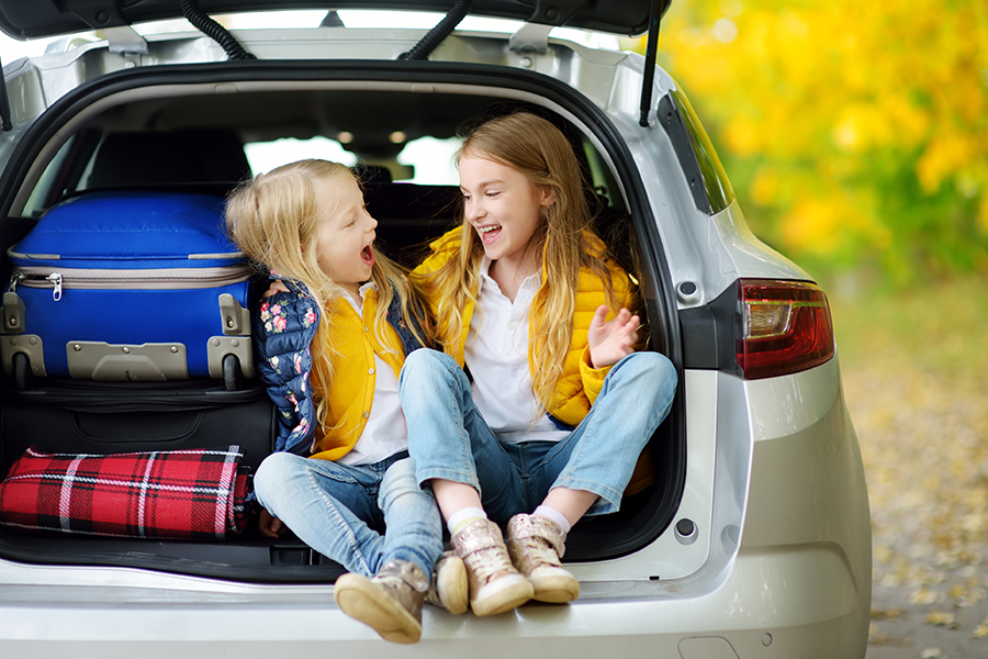 Personal Insurance - Two Young Girls Sitting in the Back of a Car with a Suitcase Getting Ready to go Camping with Their Parents